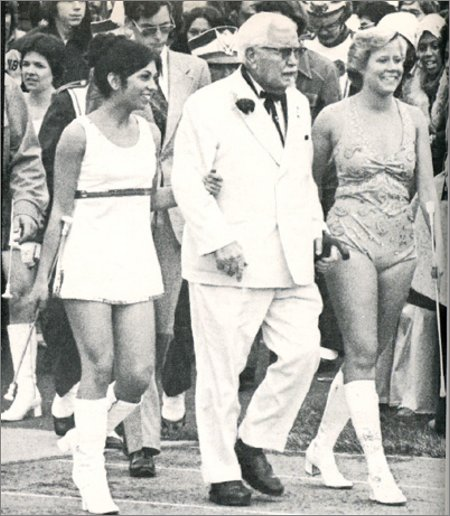 yes, it's colonel sanders with two cheerleaders